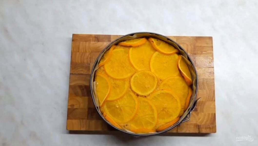 7. Форму для выпекания снизу и по бокам застелите пергаментной бумагой. По бакам выложите нарезанные и проваренные апельсины, затем залейте тесто. Сверху тоже выложите апельсины. Выпекайте в разогретой до 200 градусов духовке 50-60 минут.