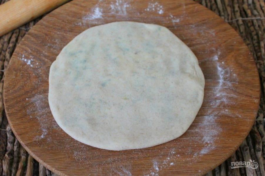 Тесто с картофелем немного прижимаем рукой и аккуратно раскатываем лепешку.