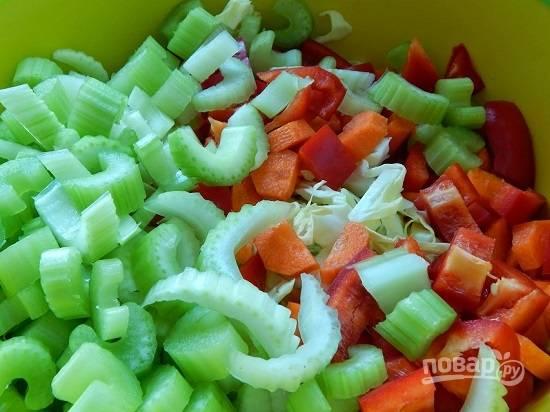 Мелко нашинкуем белокочанную капусту. Очистим морковь и очистим перец от сердцевины с семенами, нарежем морковь, перец и сельдерей на небольшие кусочки.