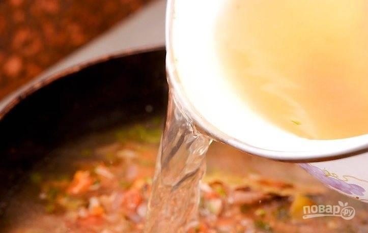 К обжаренным овощам влейте бульон, накройте крышкой и протушите 10 минут.