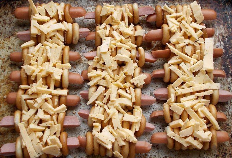 Теперь нарезаем сыр на небольшие кусочки (можно натереть) и выкладываем его на сосиски.