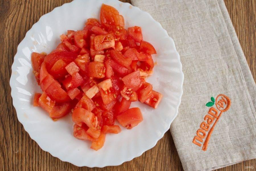 На помидорах сделайте крестообразный надрез, залейте кипятком на 2 минуты. Снимите кожицу, нарежьте крупными кубиками.