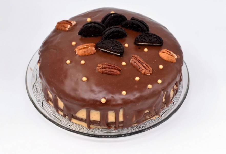Для глазури растопите плитку молочного шоколада, поломав ее на мелкие кусочки и добавив сливочное масло. Удобно растапливать шоколад в микроволновке короткими импульсами по 10-15 секунд, перемешивая каждый раз. Полейте торт глазурью, украсьте и уберите в холодильник хотя бы на пару часов.