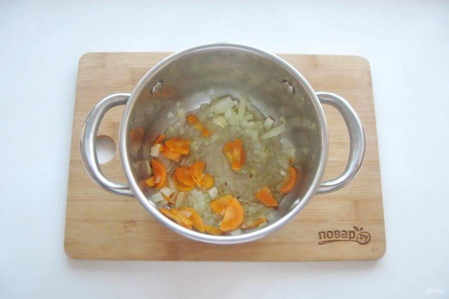 Накройте кастрюлю крышкой и тушите морковь с луком 7-8 минут на небольшом огне.