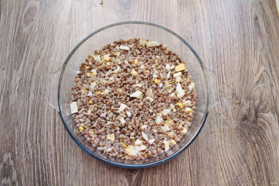 Форму для выпечки диаметром 22 сантиметра смажьте растительным маслом и обсыпьте сухарями. Положите гречку с яйцами и разровняйте.