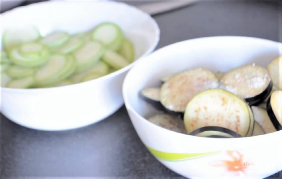 1. Нарежьте кружочками баклажаны и кабачки. Посолите их. Нарежьте кружочками помидоры, а сыр нарежьте тонкими пластинками.