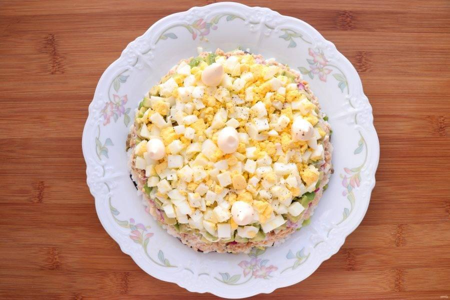 Следующим слоем выложите нарезанные яйца, посолите и поперчите по вкусу, смажьте майонезом.