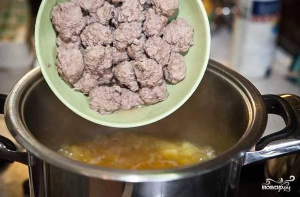 7. Бульон процедите несколько раз и снова поставьте на огонь. Выложите остальные ингредиенты супа и варите его почти до готовности. После добавьте в кастрюлю фрикадельки.