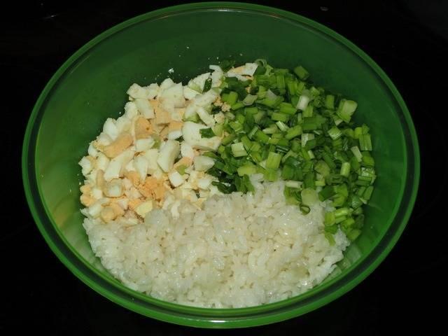 3. Сваренные вкрутую яйца остудить и очистить. Нарезать небольшими кубиками и соединить с луком. Также добавить немного остывший рис.