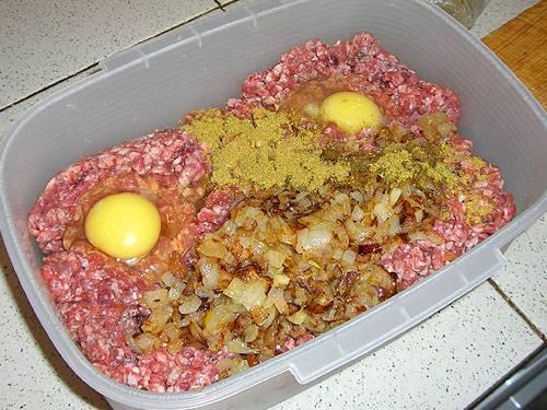 2. Фарш разморозим, добавим к нему яйца, смесь со сковороды (вместе с вытопленным жиром), а также соль, перец и приправы по вкусу. Перемешаем.
