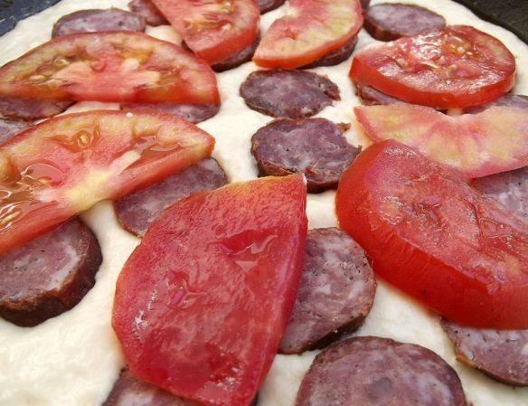 2. Выложите его равномерно на  смазанную растительным масло сковороду. Хорошо брать емкость с антипригарным покрытием или толстым дном. Сверху выложите колбасу, помидоры и сыр. По желанию, можете посыпать зеленью петрушки или добавить оливки, так ваша пицца приобретет более пикантный вкус. Я люблю добавлять итальянские травы.