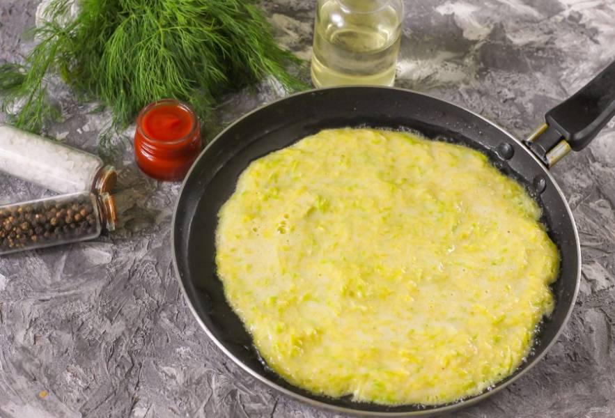 Раскалите сковороду и влейте на нее растительное масло. Прогрейте его и убавьте нагрев до среднего. Аккуратно выложите кабачковое тесто на сковороду и разровняйте в виде круга. Обжарьте около 2 минут до румяной корочки.
