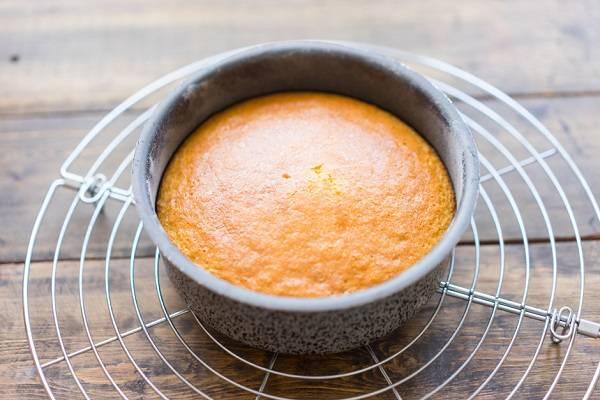 7. Жаропрочную форму смажьте немного маслом и присыпьте мукой. Выложите тесто и отправьте в разогретую до 180 градусов духовку. Готовый корж лучше всего остужать на решетке не менее 2 часов.