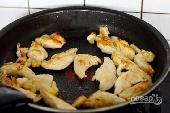 Затем добавим на сковороду масло для жарки и обжарим кусочки куриной грудки до легкого румяного цвета. Затем пусть мясо остынет.