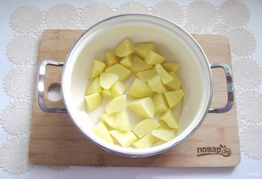 Картофель очистите, помойте и нарежьте кубиками. Выложите в кастрюлю. Отварную камбалу переложите на тарелку, а бульон процедите.