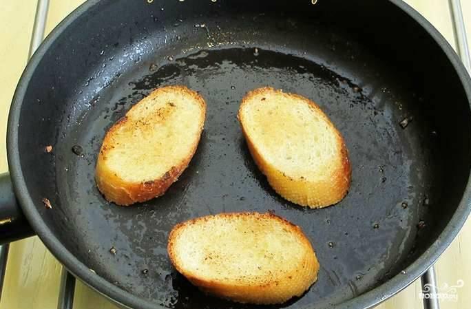 На сковороду наливаем масло. Режем багет на равные кусочки. Обжариваем их с обеих сторон и натираем чесноком и специями.