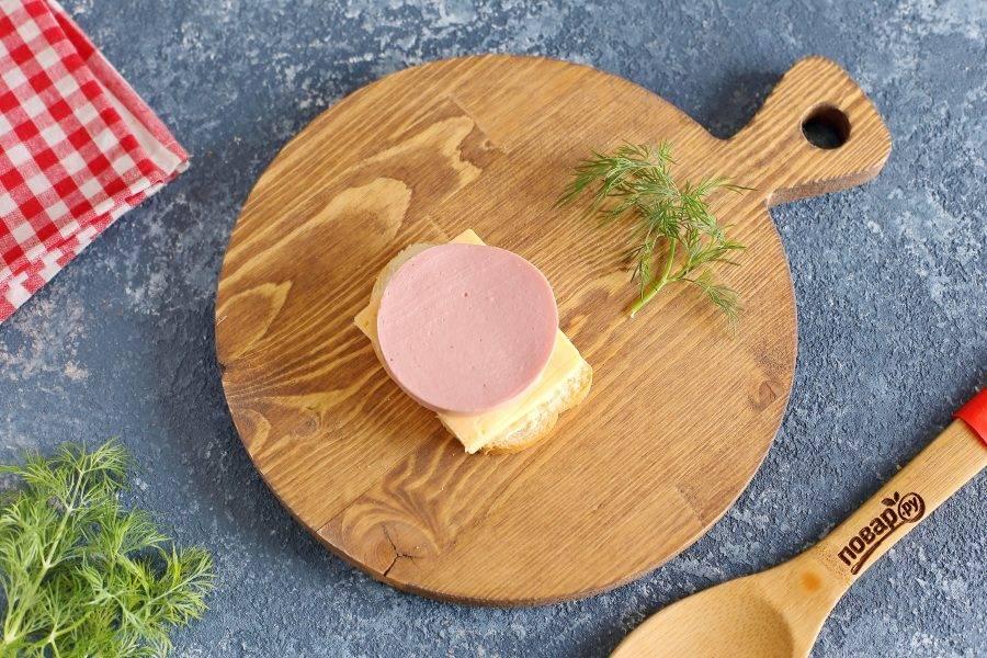 Сверху выложите кружочек колбасы на ваш вкус. Колбасу можно заменить на ветчину или буженину.