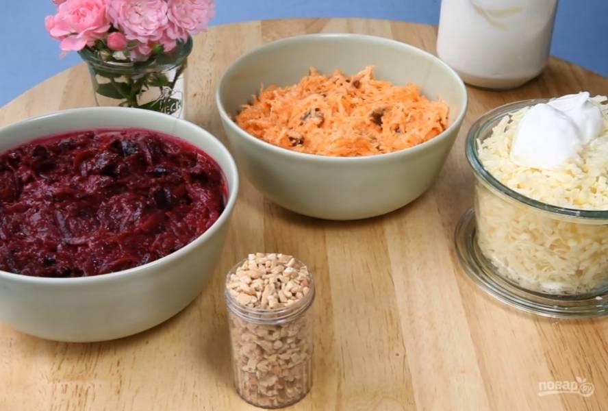 3.Для первого слоя добавьте изюм в морковь и смешайте с майонезом. Для второго слоя выдавите чеснок в сыр и смешайте с майонезом, для третьего слоя добавьте нарезанный чернослив в свеклу и смешайте с майонезом.