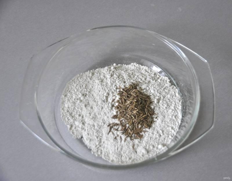 В стеклянную или керамическую посуду, которая должна быть с крышкой, всыпьте муку, добавьте тмин и перемешайте.