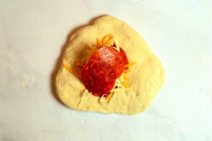 9.Каждый кусочек теста раскатайте в небольшую лепешку, по центру выложите несколько ломтиков колбасы, затем добавьте 2 вида сыра.