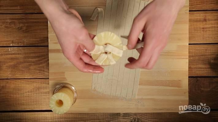 2. Делим тесто на длинные полосочки, заворачиваем в них кольца ананаса.