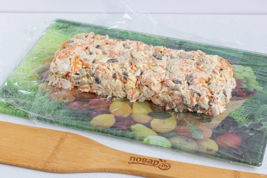Досочку застелите пищевой пленкой, выложите на неё салат и сформируйте прямоугольник. Оберните салат пищевой пленкой и уберите в морозильную камеру на 30 минут.