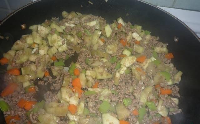 Отжимаем кусочки баклажан и добавляем на сковороду.
