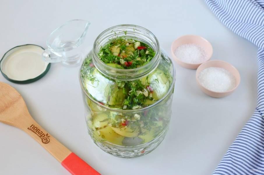 Наполните банку фаршированными помидорами, сверху выложите оставшуюся зелень с чесноком и перцем.