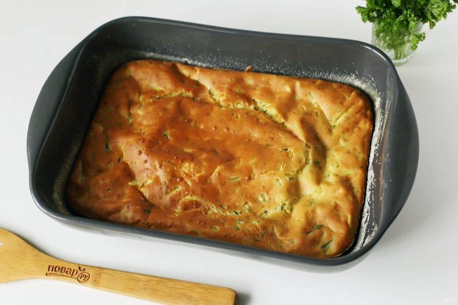 Готовому заливному пирогу с кабачком дайте немного остыть, затем нарежьте его на порции и подавайте к столу.