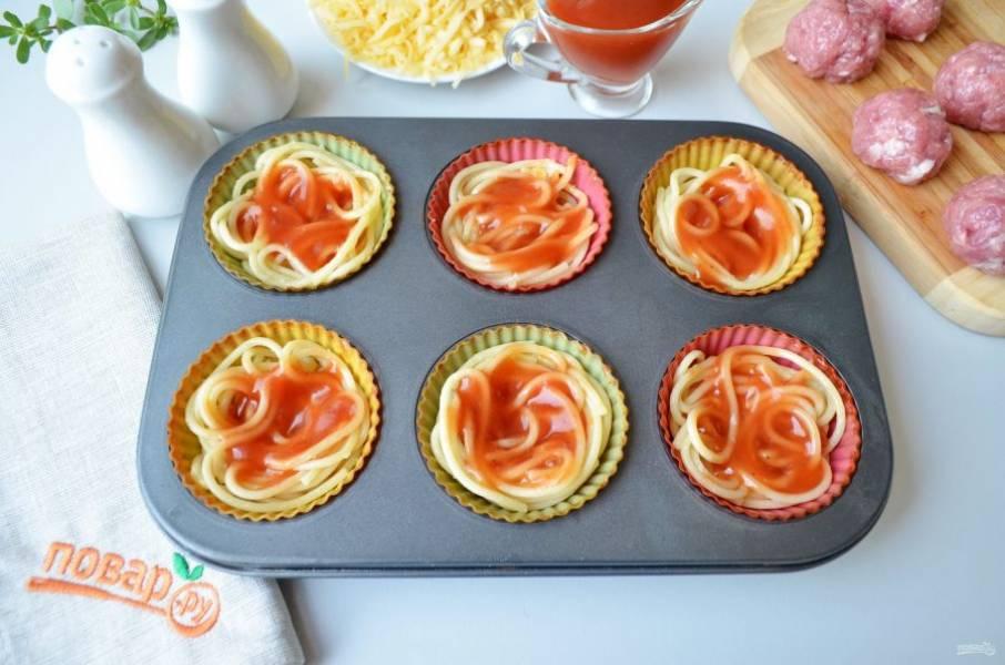 Отварные спагетти горячими смешайте с небольшой частью сыра тертого и сразу перемешайте, чтобы сыр расплавился и немного скрепил спагетти. Возьмите форму для маффинов (я проложила силиконовые вкладки, чтобы спагетти не прилипли). Разложите спагетти по формочкам (12 шт) и сверху распределите по столовой ложке томатного соуса.