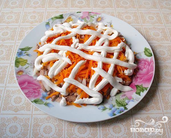 4.Отваренную морковь натираем на крупной терке поверх слоя с луком. Тонкую сметанную сеточку наносим поверх моркови.