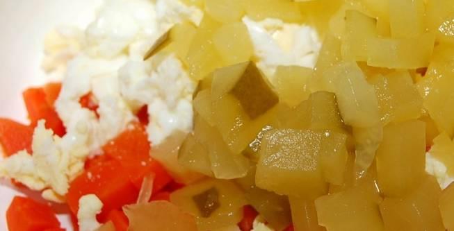 1. Для начала подготовим ингредиенты. Морковь и яйца отварим и остудим. Горошек и рыбу разморозим, авокадо помоем. Смешаем отваренную порезанную кубиками морковь и тертые яйца. Сюда же добавляем измельченный маринованный огурец.