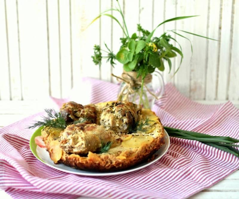 Картофельный кугель выложите на блюдо, сверху уложите рулетики. Подавайте  со свежей зеленью и салатом или маринованными овощами.