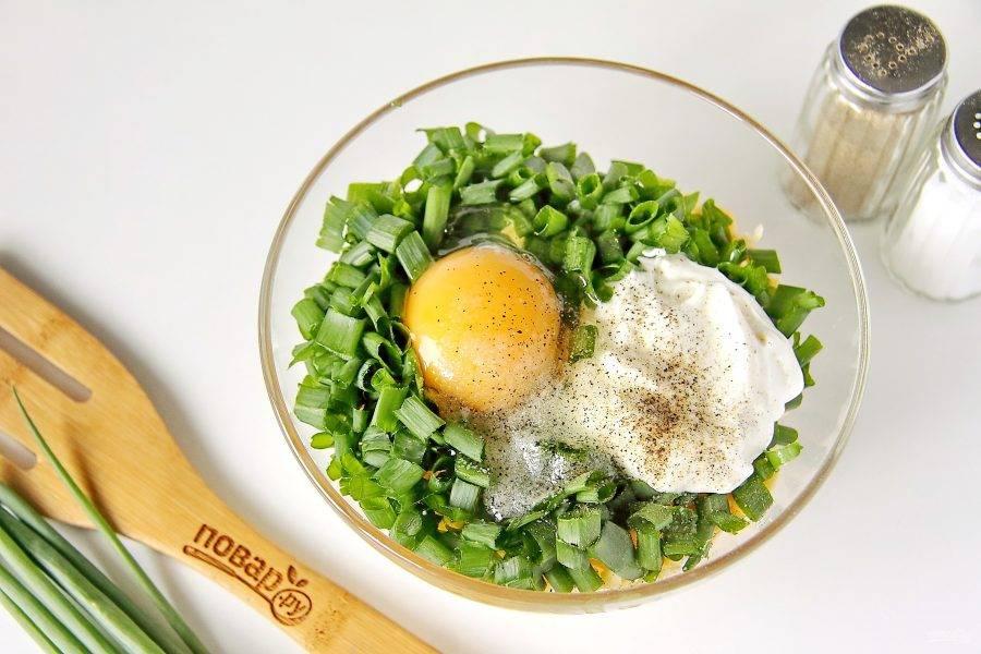 Лук измельчите ножом, добавьте сметану, одно сырое яйцо, соль и молотый перец по вкусу.