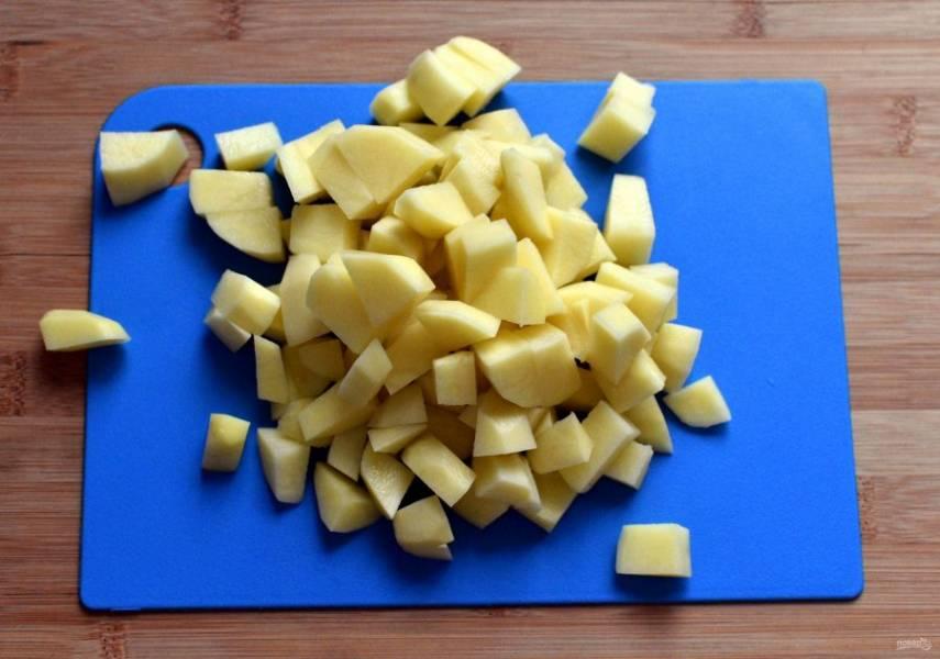Сварите насыщенный бульон из говяжьей лопатки. Процедите бульон, отмерьте 2 литра, мясо нарежьте кусочками. Картофель нарежьте кубиками среднего размера и опустите в бульон. Варите почти до готовности картофеля.