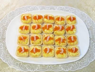 Выложите салат в тарталетки и украсьте икрой и креветками.