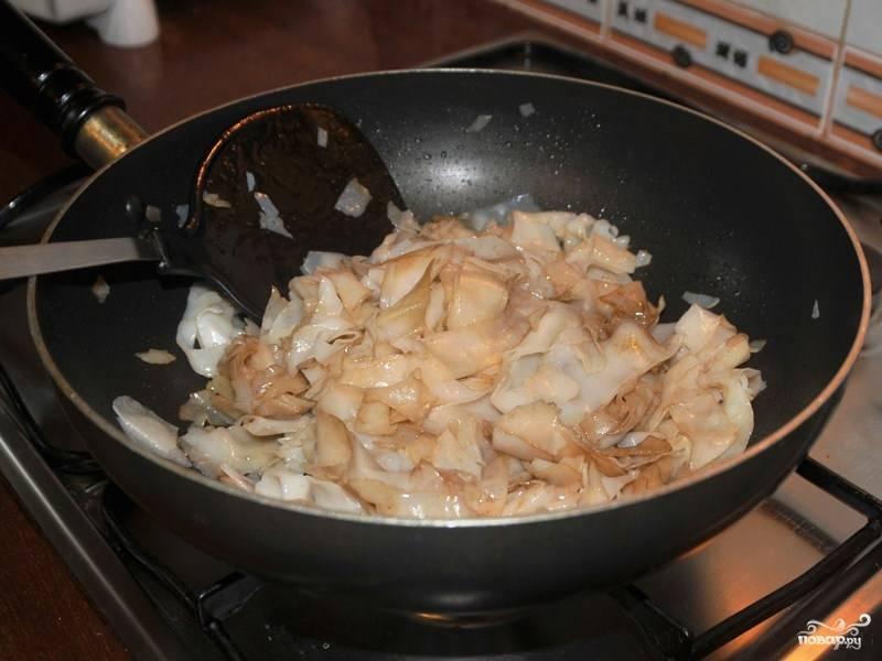 Добавьте соевый соус и, помешивая, жарьте лапшу минут 5.