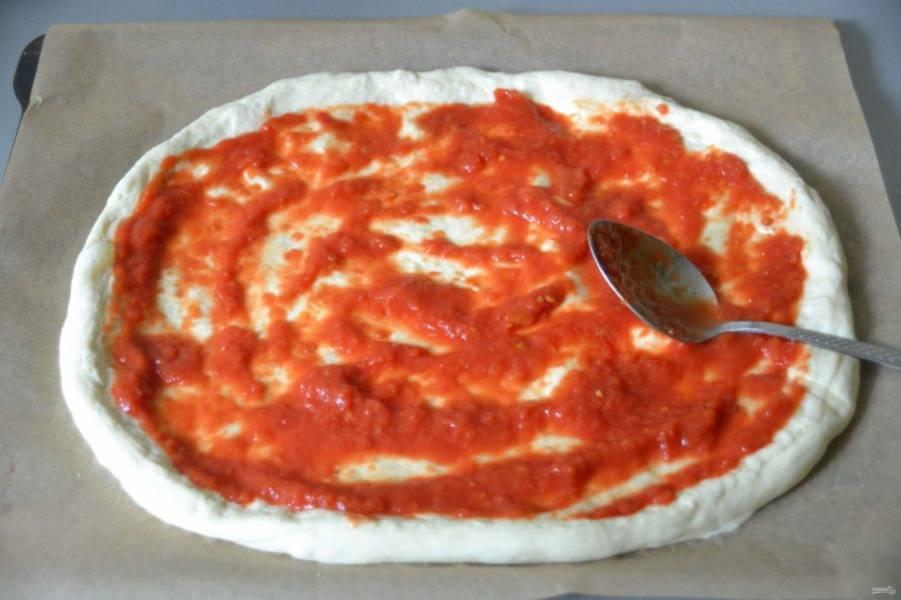 Нанесите на основу для пиццы томатную пассату, делайте это обратной стороны ложки, разравнивая по всей поверхности.