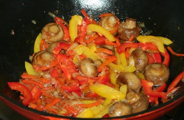 Режем перец тонкими полосками и добавляем на сковороду, тушим еще 5 минут. Также кладем: соль и по 1/3 чайной ложки куркумы, паприки, базилика, майорана.