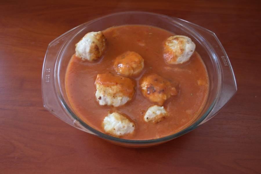 Смешайте томатный сок с 1 ст. ложкой крахмала. Добавьте сахар, соль, перец, специи по вкусу. Полученным соусом залейте тефтели. Накройте форму крышкой или фольгой. Запекайте тефтели в горячей духовке при 200 градусах 30 минут.