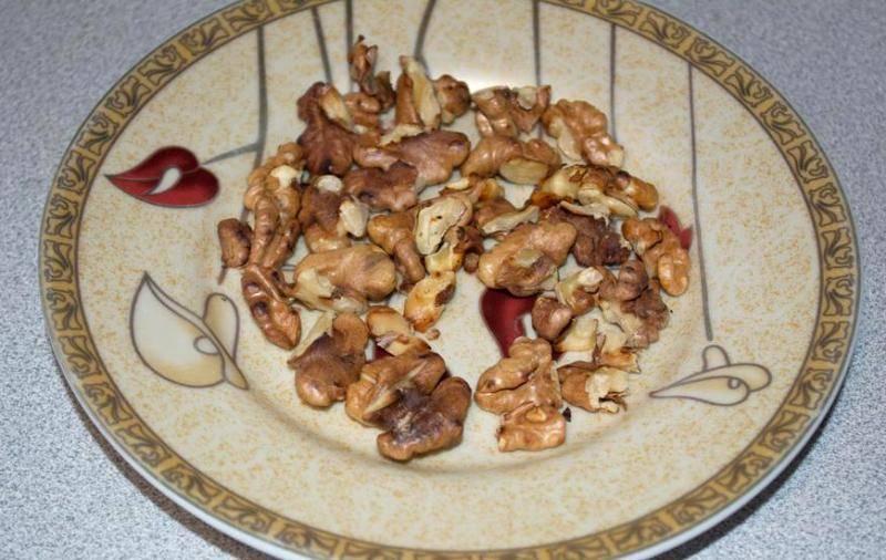Грецкие орехи выкладываем на сухую сковороду и прогреваем их несколько минут, потом разламываем орехи на небольшие кусочки.