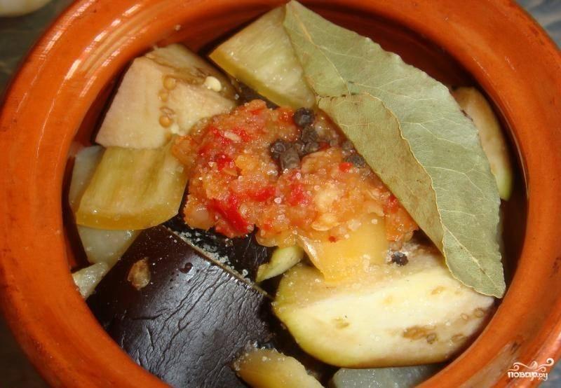 Затем добавляем мелко нарезанный чеснок, лавровый лист, перец горошком, слегка солим и добавляем специи. Я положила по ложечке готовой аджики в каждый горшочек.