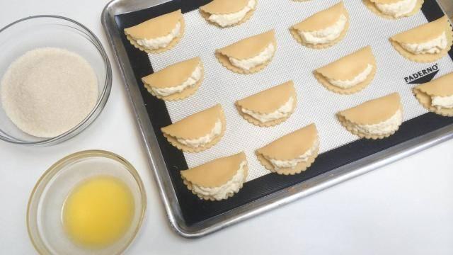 Печенье выложите на противень. Помажьте яйцом и посыпьте сахаром.