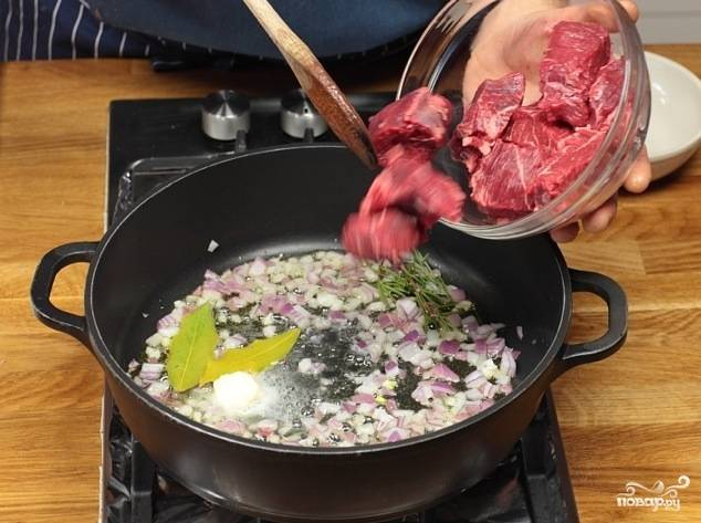 В сковороде разогреть оливковое масло, растопить в нем сливочное. Обжарить лук и лавровый лист в течение пары минут, после чего добавить говядину и жарить на среднем огне, помешивая, пока мясо со всех сторон не поменяет цвет.