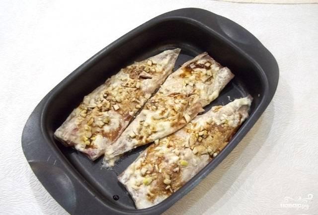 9.Форму для запекания смазываем маслом, укладываем в неё маринованные кусочки рыбы. Сбрызгиваем соевым соусом. Теперь мелко нарезаем чеснок, выкладываем его на рыбу.