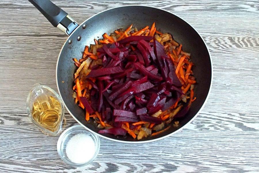 Нарежьте свёклу брусочками и добавьте в сковороду с луком и морковью.  Добавьте 1,5 половника бульона или воды, соль, сахар, уксус. Включите огонь чуть ниже среднего. Нагревайте до закипания.