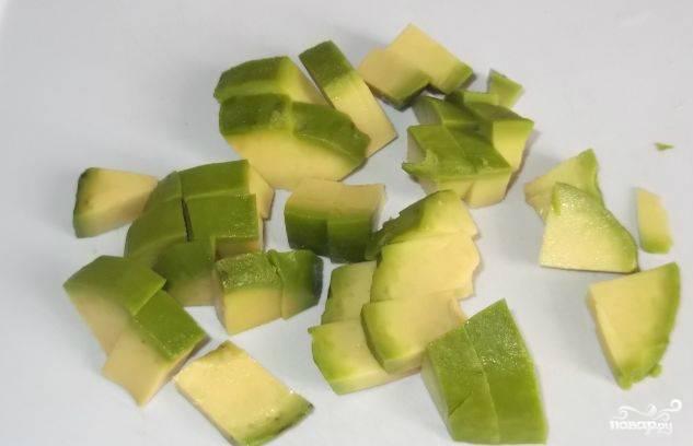 Очищаем авокадо от твердой корочки. Режем пополам, вынимаем косточку. Затем мякоть авокадо нарезаем ножом.