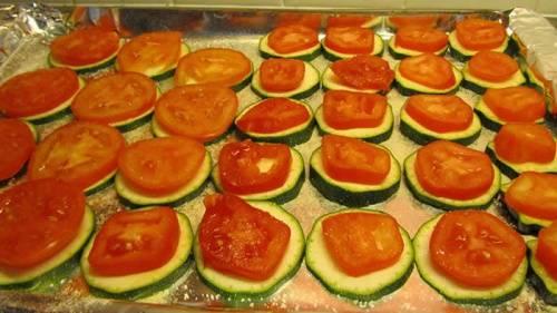 Теперь разогреваем духовку до 170 градусов Цельсия. Противень застилаем фольгой, с помощью кухонной кисточки смазываем ее растительным маслом и выкладываем кружочки кабачков. Каждый посыпаем солью и укладываем помидоры. Затем снова солим, добавляем черный молотый перец и сыр.