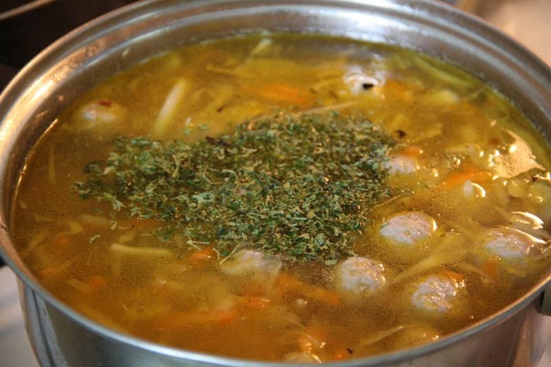 7. Влить воду, довести до кипения и выложить фрикадельки. Посолить и поперчить по вкусу. Можно добавить лавровый лист или специи. Варить капустный суп с фрикадельками в домашних условиях около 10-13 минут, а затем оставить под закрытой крышкой настояться еще минут 15. Перед подачей можно присыпать свежей или сушеной зеленью.