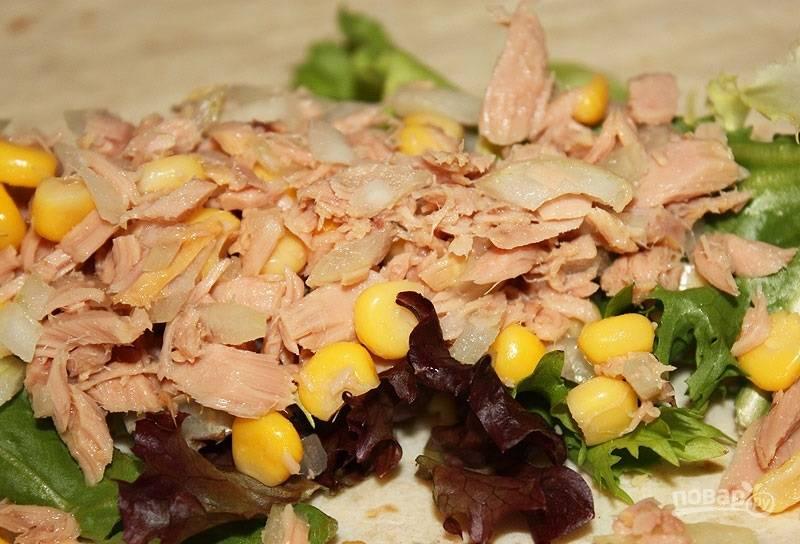 3.В отдельной миске смешиваю консервированный тунец без сока, измельченный репчатый лук и консервированную кукурузу. Выкладываю смесь на салатные листья.
